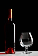 Bottle of red wine and an empty glass on table