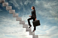 Businesswoman stepping up a stairway