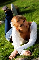 Beautiful young woman laying on the grass.