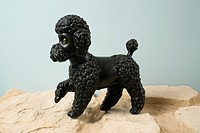 A kitsch dog figurine with paw raised