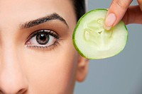 Woman with a cucumber next to her eye
