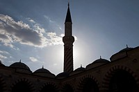The minaret of a mosque back lit by the sun