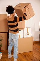 A woman lifting a moving box and placing on a stack of boxes