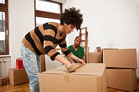 A woman taping a moving box while a man watches