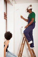 A man standing on a ladder using a paint roller while a woman watches