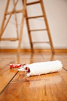 A paint roller on a hardwood floor, ladder in background (thumbnail)