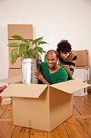 A woman pushing a man sitting inside of a moving box (thumbnail)