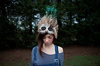 Young woman with feathered mask on her head