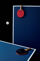 Table tennis tables, bats and a ball mid_air