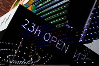 An illuminated 23h OPEN sign on the outside of a building