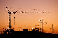 A construction crane and electricity pylons silhouetted against a sunset sky