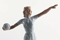 A vintage porcelain statue of a woman preparing to throw a ball