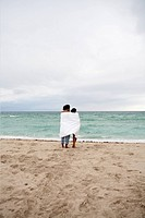 A young couple wrapped in a beach towel standing on the beach