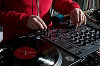 A DJ adjusting knobs on a sounder mixer, detail of hands