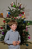 A young boy standing in front of a decorated Christmas tree
