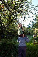 Girl on mother´s shoulders in orchard