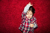 A young smiling boy lying on a red carpet