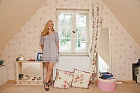 A teenage girl standing in her bedroom smiling