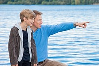 A father pointing something out to his son, outdoors
