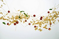 Raw pasta, tomatoes, and basil against a white background