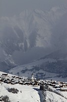 Snowy village with mountain range and valley in the background (thumbnail)