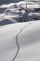 Snow footprints on hill with electric pylon in background