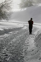 Lone hiker walking along snow path