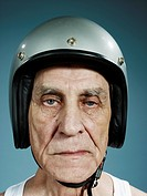 A headshot of a frowning senior man wearing a crash helmet