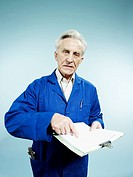 A senior man wearing coveralls and pointing to a paperwork on a clipboard