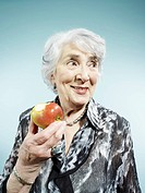 A senior woman holding an apple with a bite out of it