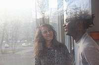 A boyfriend and girlfriend laughing together, viewed through window