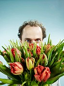 A man nervously hiding behind a bouquet of tulips (thumbnail)