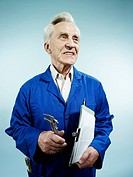 A cheerful senior man in coveralls carrying a clipboard and work tool (thumbnail)