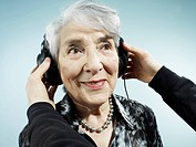A person putting headphones on a senior woman