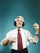 A senior man wearing headphones and playing air guitar