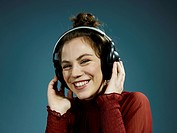 A young hip woman wearing headphones and smiling