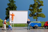 A diorama of a miniature worker billboard posting