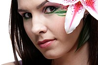 portrait of beautiful brunette with eye_zone body art posing with tiger lily