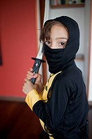 A boy dressed in a ninja costume holding a samurai sword