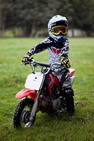 A boy in protective sportswear sitting on a dirt bike
