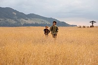 A teenage boy running with his younger brother in a field