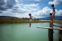 A boy jumping into water while his twin brother and friend watch (thumbnail)