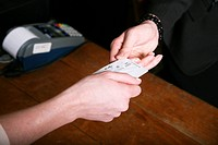 A woman paying with a credit card in a shop, close_up of hands