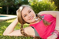 Spain, Mallorca, Teenage girl lying in grass, smiling, portrait