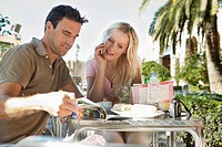 Spain, Mallorca, Palma, Couple sitting at table in cafe, smiling