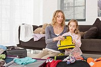 Germany, Leipzig, Mother and daughter packing suitcase for vacation (thumbnail)