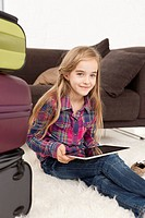 Germany, Leipzig, Girl using digital tablet and with suitcase, smiling, portrait