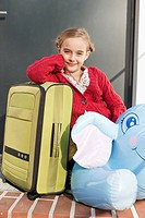 Germany, Leipzig, Girl with packed luggage, smiling, portrait