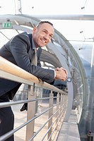 Germany, Leipzig, Businessman leaning on railing, smiling (thumbnail)