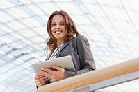 Germany, Leipzig, Businesswoman using digital tablet, smiling, portrait
